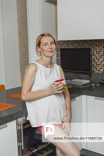 Porträt einer lächelnden Frau  die einen Becher hält  während sie sich in der Küche an den Tresen lehnt.