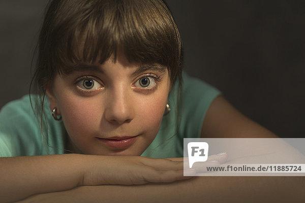 Nachdenkliches Mädchen mit gekreuzten Armen auf grauem Hintergrund