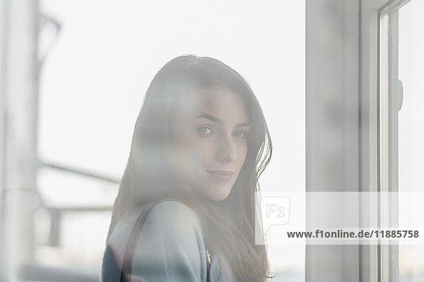 Porträt einer jungen schönen Frau mit langen Haaren durch ein Glasfenster gesehen