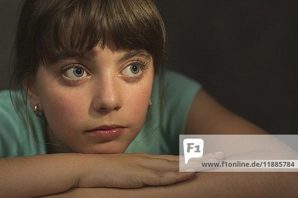 Nachdenkliches Mädchen,  das sich ausruht,  während es vor grauem Hintergrund wegschaut