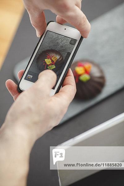 Beschnittenes Bild eines Mannes  der das Dessert auf dem Tisch mit dem Handy fotografiert.
