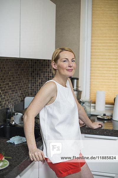 Lächelnde Frau an der Theke in der Küche