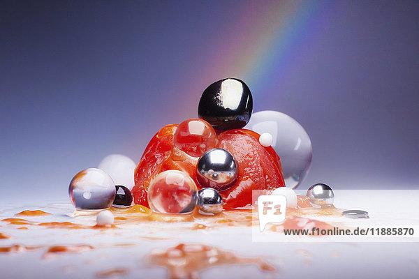 Zerschmetterte Tomate über glänzenden Murmeln und Kugeln vor mehrfarbigem Hintergrund