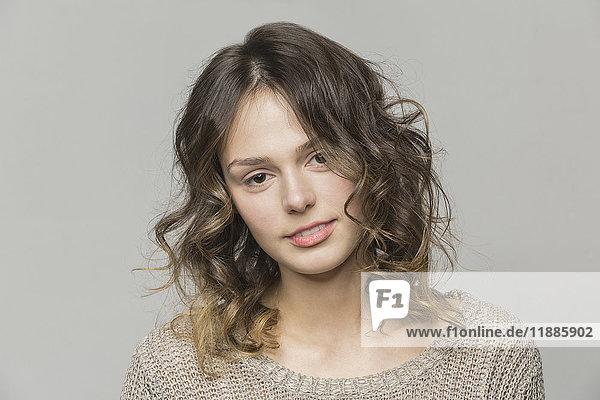 Porträt einer schönen Frau mit einem auf grauem Hintergrund gespannten Kopf
