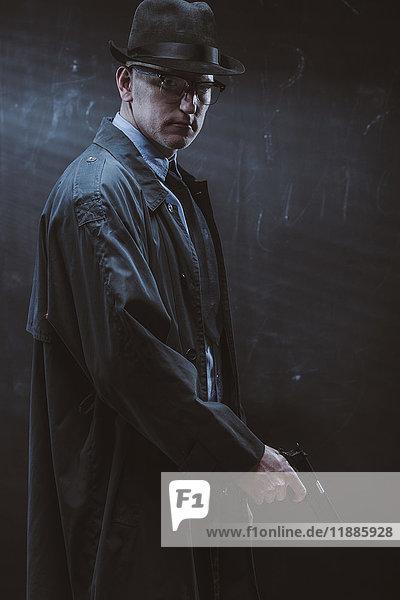 Porträt eines selbstbewussten Mannes  der die Waffe an der schwarzen Wand hält.