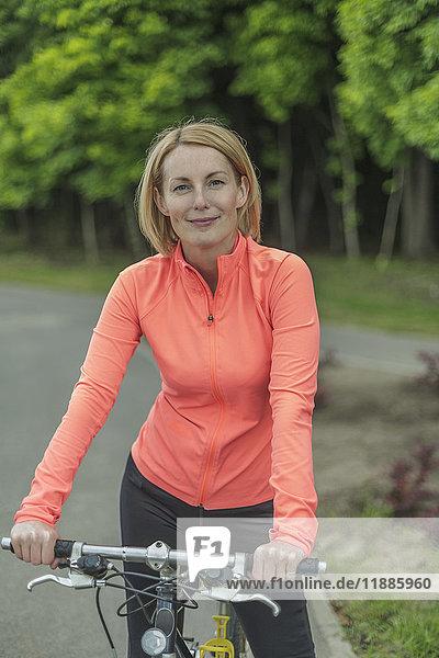 Porträt einer lächelnden Frau mit Fahrrad auf dem Weg zum Park gegen den Himmel