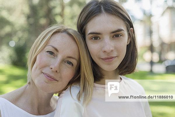 Porträt der lächelnden Mutter und Tochter im Park