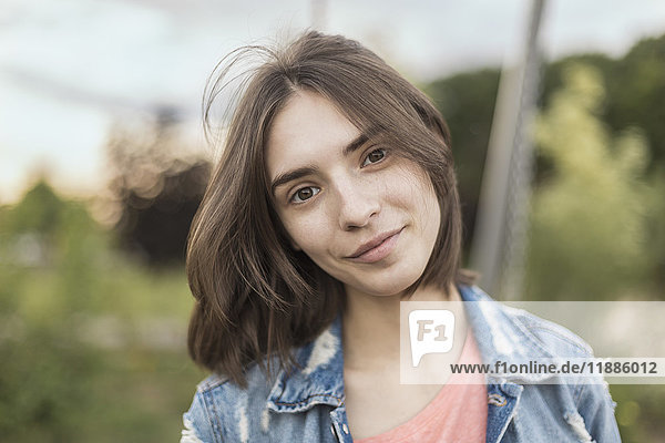 Portrait of smiling young woman with head cocked at park