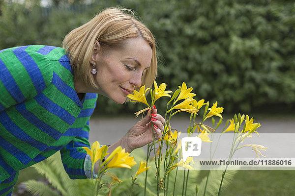 Seitenansicht einer reifen Frau  die im Park gelbe Blumen riecht.