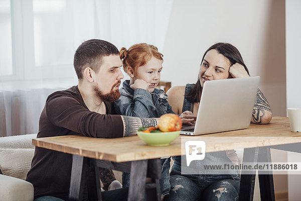 Eltern zeigen der Tochter den Laptop  während sie zu Hause auf dem Sofa sitzen.