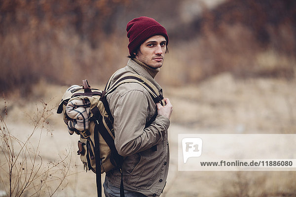 Porträt eines Mannes mit Rucksack und stehendem Feld