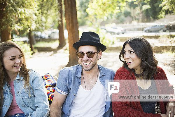 Glückliche männliche und weibliche Freunde sitzen auf einer Bank im Park.