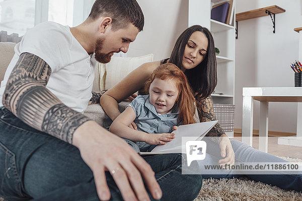 Eltern sehen sich das Buch an  während sie zu Hause auf dem Teppich sitzen.