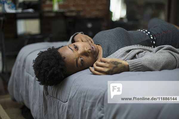 Junge Frau zu Hause auf dem Bett liegend