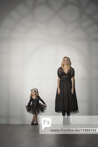Portrait von Mutter und Tochter in schwarzem Kostüm an der Wand stehend im Tanzstudio