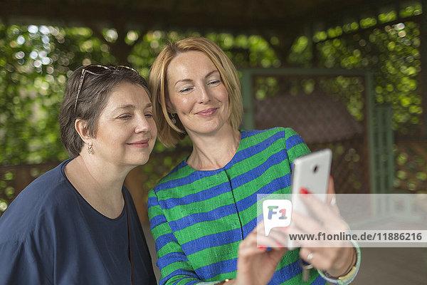 Lächelnde Frau  die Selfie mit Mutter im Pavillon nimmt