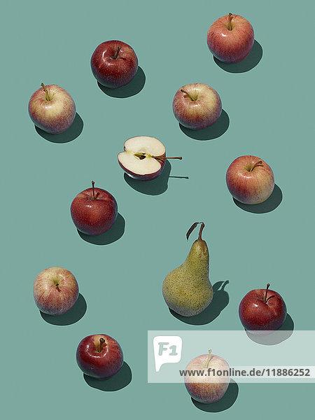 Hochwinkelansicht der Birne inmitten von Äpfeln auf blauem Grund