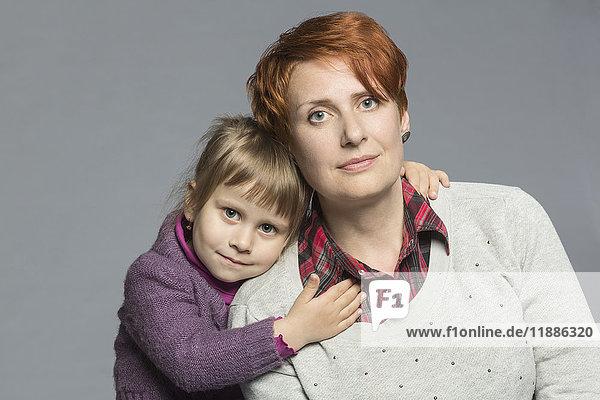 Porträt der Tochter  die die Mutter vor grauem Hintergrund umarmt.