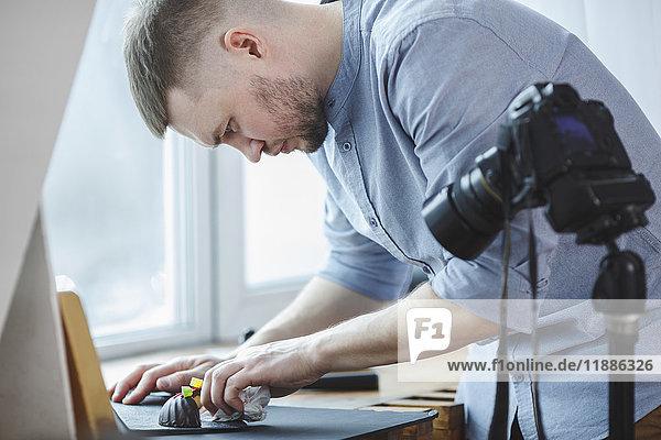Mann  der im Studio mit einer Stativkamera den Teller putzt.