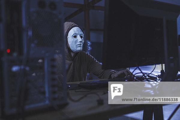 Mann mit Maske und Kapuze mit Computer am Tisch