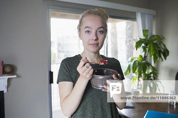 Porträt einer Frau beim Frühstücken zu Hause