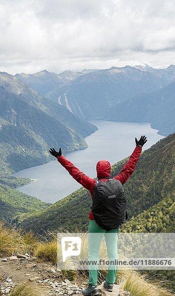 Wanderin schaut auf den South Fiord des Lake Te Anau  streckt Arme in die Luft  hinten Südalpen  am Wanderweg Kepler Tack  Fiordland National Park  Southland  Neuseeland  Ozeanien