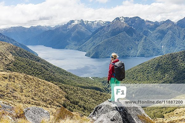 Female hiker looking at the South Fiord of Lake Te Anau  Southern Alps at back  Kepler Tack  Fiordland National Park  Southland  New Zealand  Oceania