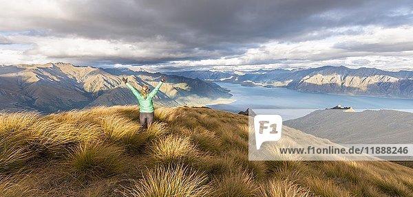Wanderin streckt Arme in die Luft  Lake Hawea und Berglandschaft  Isthmus Peak  Otago  Südinsel  Neuseeland  Ozeanien