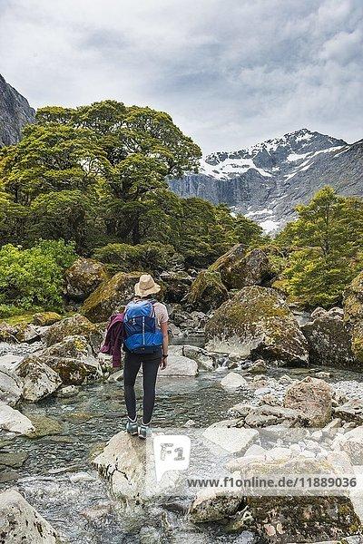 Wanderin auf Felsen im Fluss  Fiordland National Park  Southland  Neuseeland  Ozeanien