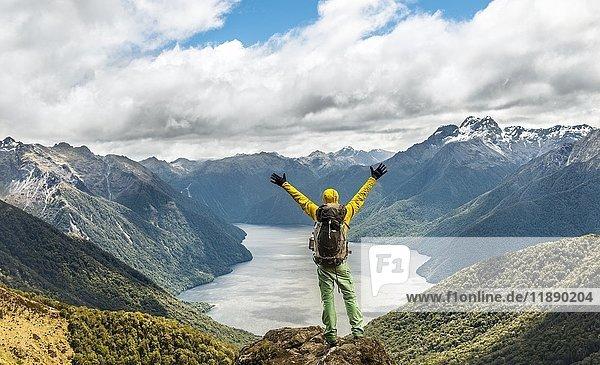 Wanderer schaut auf den South Fiord des Lake Te Anau  streckt Arme in die Luft  hinten Südalpen  am Wanderweg Kepler Track  Fiordland National Park  Southland  Neuseeland  Ozeanien Wanderer schaut auf den South Fiord des Lake Te Anau, streckt Arme in die Luft, hinten Südalpen, am Wanderweg Kepler Track, Fiordland National Park, Southland, Neuseeland, Ozeanien