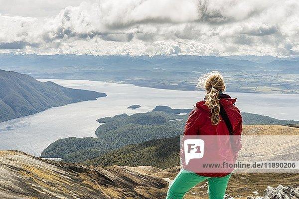 Wanderin schaut auf den South Fiord des Lake Te Anau  hinten Südalpen  am Wanderweg Kepler Tack  Fiordland National Park  Southland  Neuseeland  Ozeanien