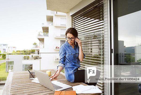Geschäftsfrau am Telefon bei der Arbeit auf dem Balkon zu Hause