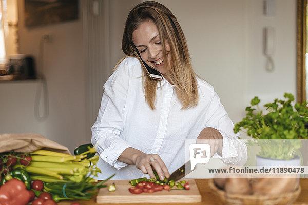 Lächelnde Frau am Telefon beim Gemüsehacken in der Küche