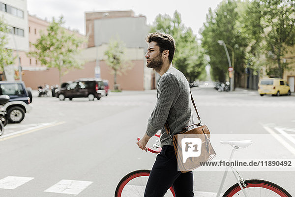 Junger Mann schiebt sein Fahrrad auf die Straße