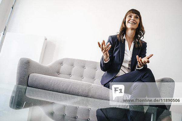 Geschäftsfrau auf der Couch sitzend  gestikulierend