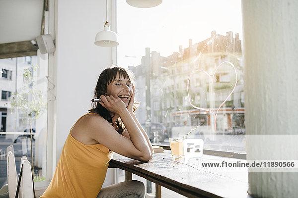 Frau im Café sitzend zeichnet Herzform auf Fensterscheibe mit Lippenstift