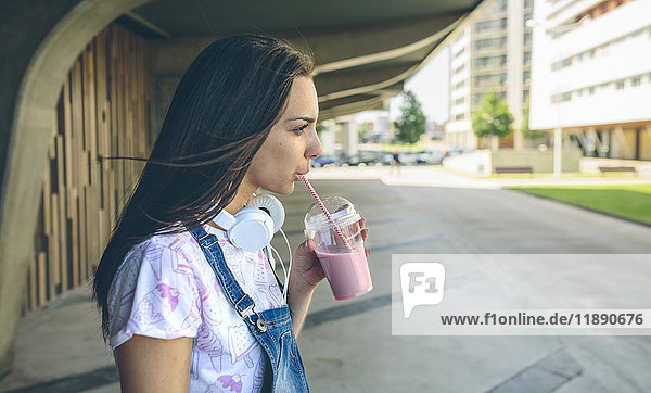 Young woman with headphones drinking strawberry smoothie