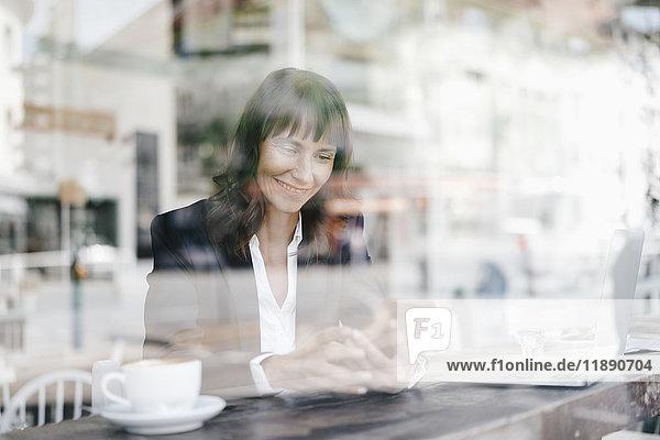 Geschäftsfrau sitzend im Cafe  mit Smartphone