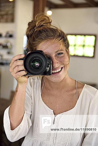 Porträt einer lachenden jungen Frau  die mit der Kamera fotografiert.