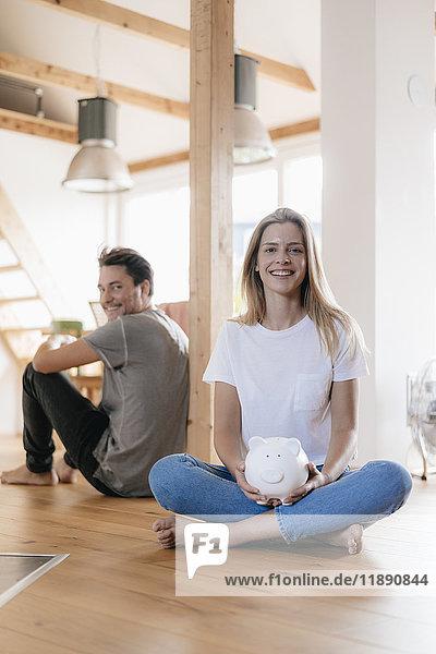 Paar sitzt in neuem Zuhause mit Sparschwein