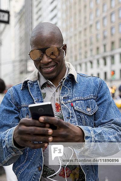 USA  New York City  Manhattan  Porträt eines Mannes mit verspiegelter Sonnenbrille auf dem Handy