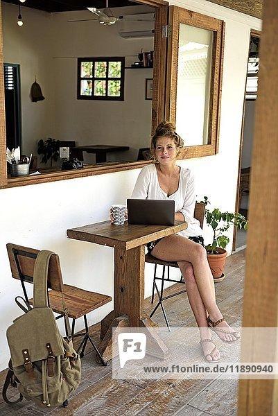 Porträt einer jungen Frau mit Laptop und Kaffeetasse auf der Veranda eines Cafés