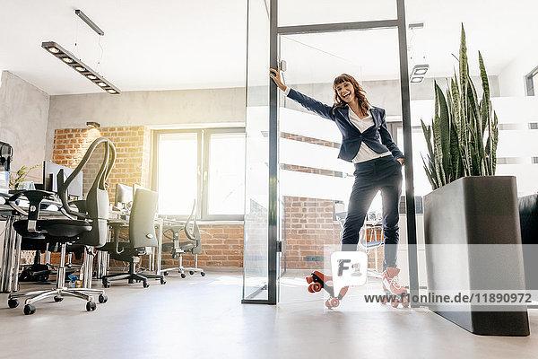 Erfolgreiche Geschäftsfrau mit Rollschuhen im Büro