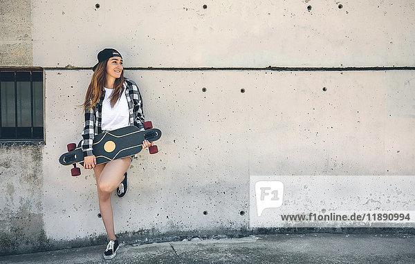 Porträt einer glücklichen jungen Frau mit Longboard vor der Betonwand stehend