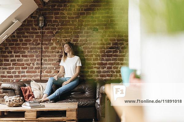 Junge Frau auf der Couch sitzend  träumend Junge Frau auf der Couch sitzend, träumend