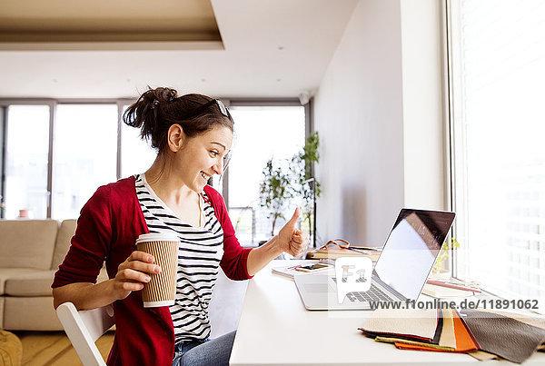 Lächelnde Frau mit Kaffee für zu Hause am Schreibtisch