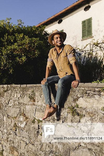 Lächelnder Mann sitzt an der Wand bei Sonnenlicht