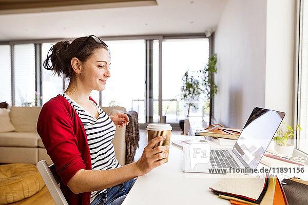 Lächelnde Frau mit Kaffee zum Mitnehmen im Home Office