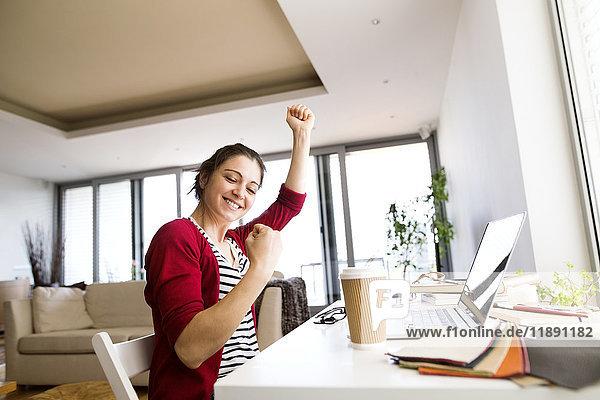 Glückliche Frau am Schreibtisch zu Hause
