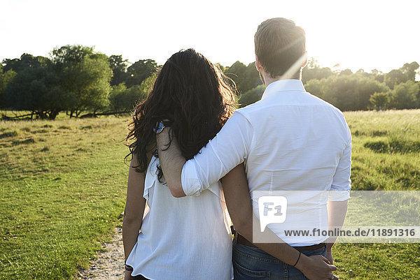 Rückansicht des jungen Paares Arm in Arm bei Sonnenuntergang